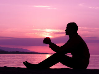 Photo of a person in prayer against a pink sunrise