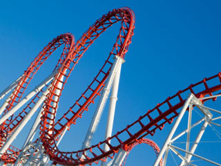 A photo of a red rollercoaster against a blue sky