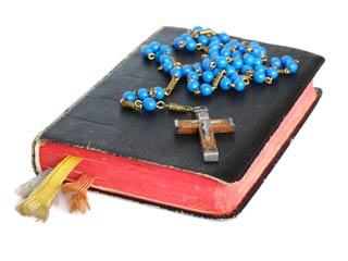 A photo of a blue rosary and a bible