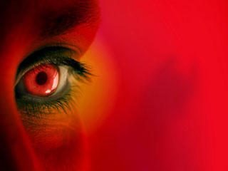 A photo a face with red eyes on a red background