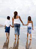 Photo of a single mother walking on the beach with two children