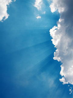A photo of a bright blue sky with the sun's rays peeking from behind a puffy white cloud