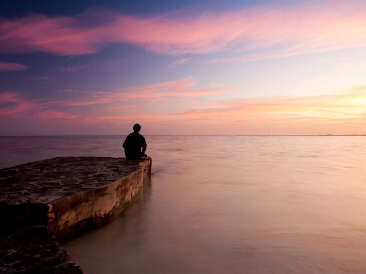A photo of a man sitting near the water
