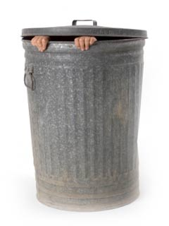 A photo of a trash can with two hands peeking through the top
