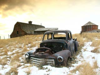 Photo of an old abandoned truck in the foreground with an old farm in the background