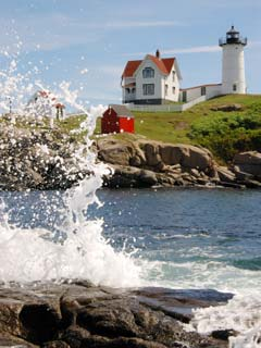 A photo of waves breaking against the rocks with a lighthouse in the background