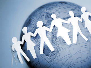 Photo of paper cutout people holding hands and surrounding the globe